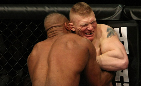 Brock Lesnar (right) winces in pain after eating a couple of knees to the breadbasket by Alistair Overeem in the main event of UFC 141 last Friday night in Las Vegas. Photo by Donald Miralle via Zuffa LLC/Getty Images.
