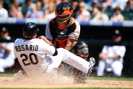 August 5, 2012; Denver, CO, USA; San Francisco Giants catcher Hector Sanchez (right) tags out Colorado Rockies catcher Wilin Rosario (20) at the plate during the fourth inning at Coors Field.  The Giants won 8-3.  Mandatory Credit: Chris Humphreys-US PRESSWIRE