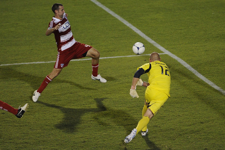 Jul 28, 2012; Frisco, TX, USA; FC Dallas midfielder Andrew Jacobson (4) tries to direct the ball past Los Angeles Galaxy goalkeeper Josh Saunders (12) during the second half at FC Dallas Stadium. Los Angeles Galaxy defeated FC Dallas 1-0. Mandatory Credit: Jerome Miron-US PRESSWIRE