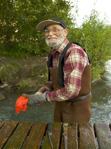 Old-man-fisherman-cleans-fish_medium