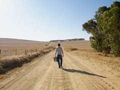 Man_walking_down_dirt_road_medium