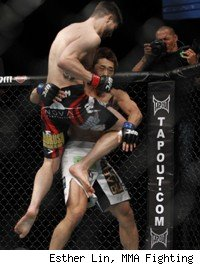 Carlos Condit throws a flying knee against Dong Hyun Kim.