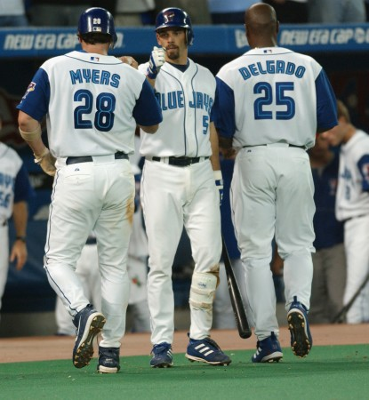 8a70aab7c Chris Woodward welcomes Greg Myers and Carlos Delgado back to the dugout  after they scored a couple of runs against the New York Yankees in a 2003  game at ...